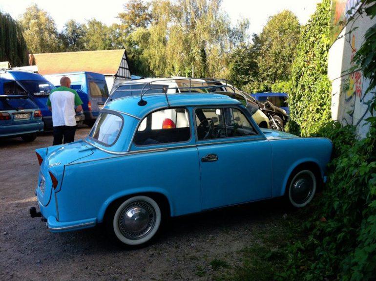 Oldtimer Berlin: Blauer Trabant vor Bäumen