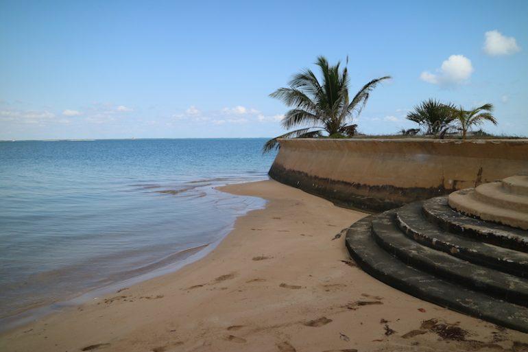 Strände Kenia: Strand, Mauer und Palme in Manda Bay
