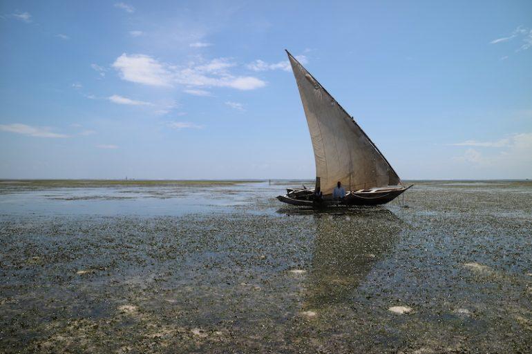 Kenia Strand: Dhow mit Mensch im Wasser am Kenyatta Beach