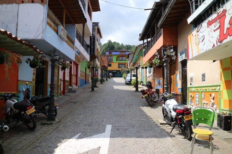 Strasse mit Motorrädern und bemalte Häuser in Guatape
