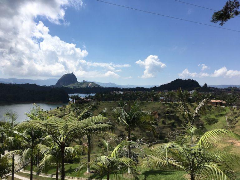 Palmen und Wasser, der Felsen von Guatapé im Hintergrund