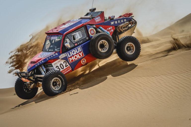 Dakar Rally in China: Buggy mit drei Rädern in der Luft in einer Düne
