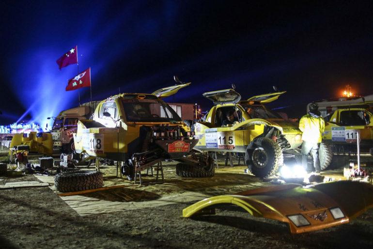 Teams schrauben nachts an ihren Fahrzeugen bei der Dakar Rally in China