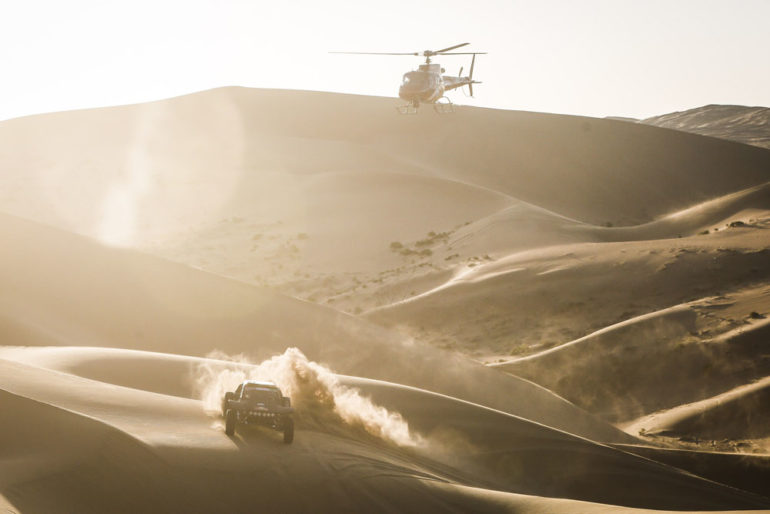 Dakar Rally in China: Helikopter über einem Buggy in den riesigen Dünen der Wüste Gobi