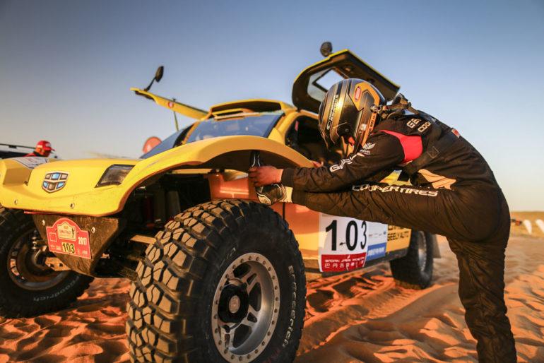 Dakar Rally in China: Ein Pilot dehnt sich am Reifen seines Buggy