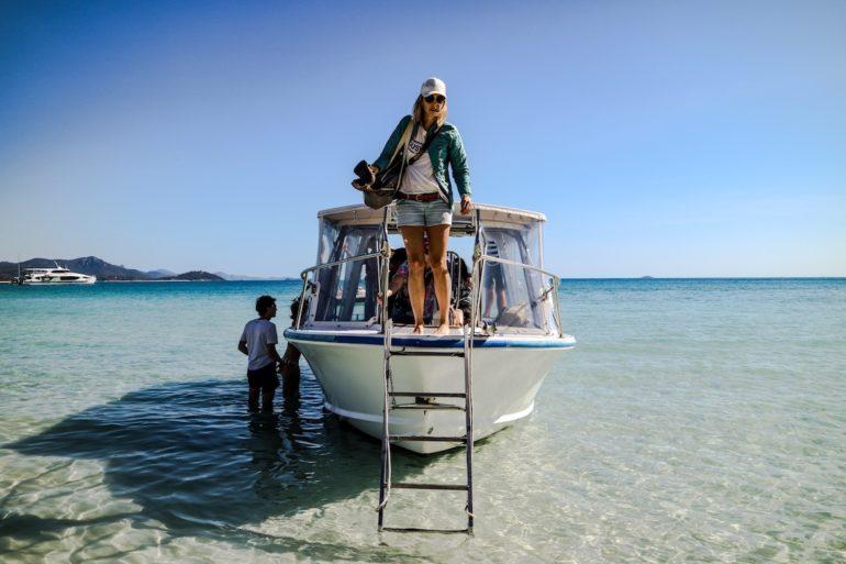 Whitsundays: Boot mit Gästen in klarem Wasser am Whitehaven Beach.