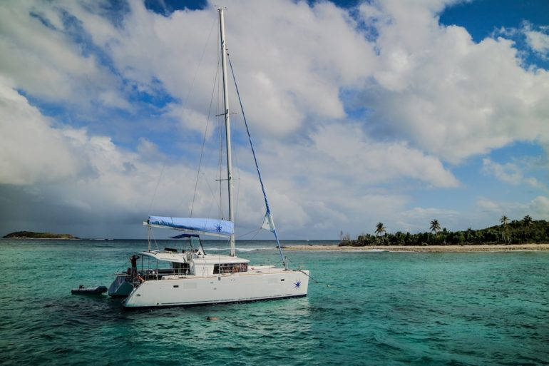 Britische Jungferninseln: Segelboot in türkisem Wasser vor einem Strand