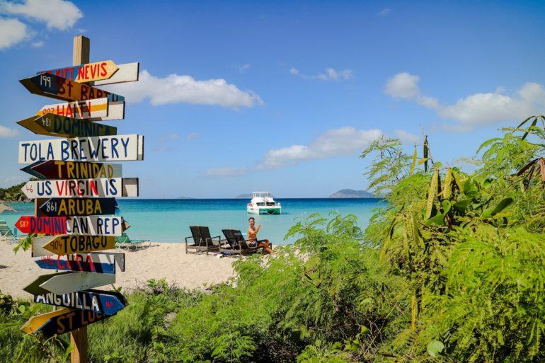 Britische Jungferninseln: Wegweiser am Strand vor türkisem Wasser am Smuggler's Cove in Tortola