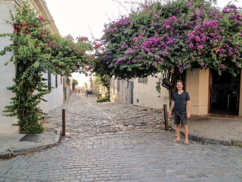 Uruguay Sehenswürdigkeiten: Marco Buch vor Gasse mit Pflanzen in Colonia del Sacramento