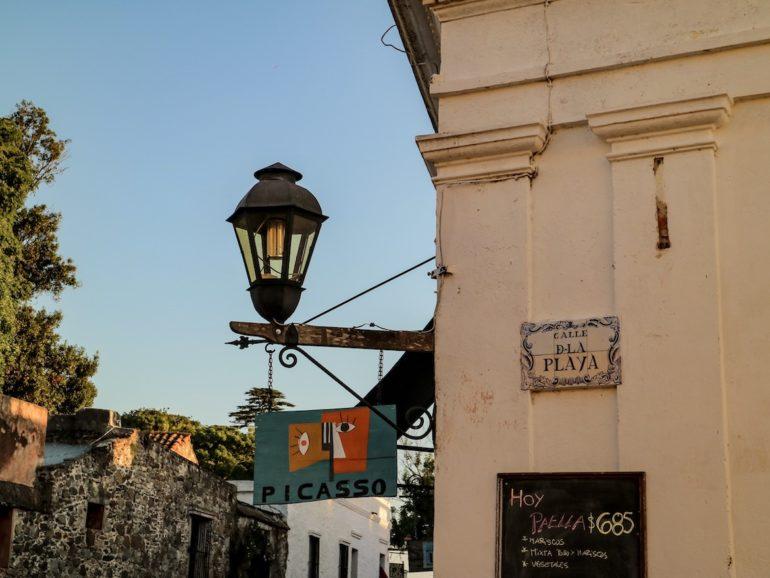 Uruguay Sehenswürdigkeiten: Strassenschild und Laterne vor alten Häusern