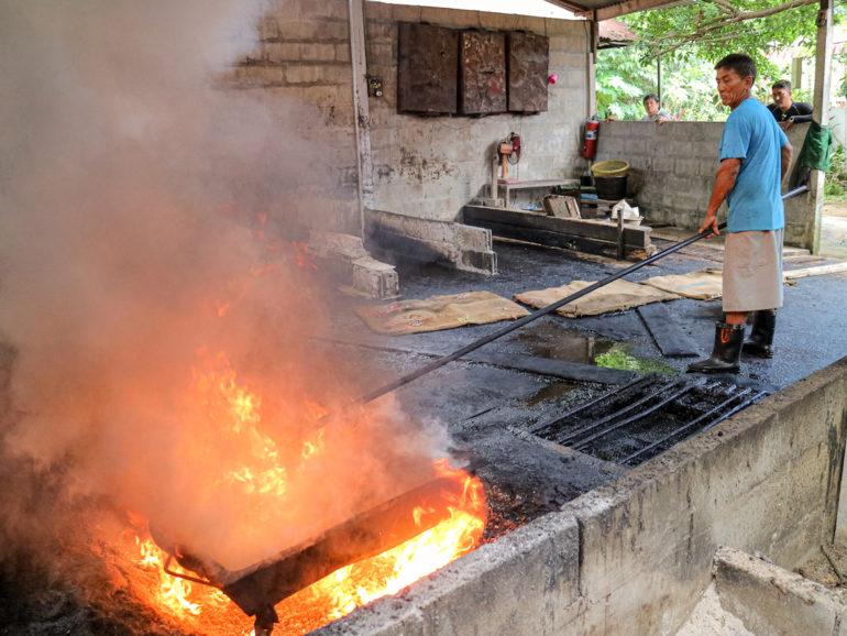 Mann röstet Cashewnüsse über einem rauchenden Feuer