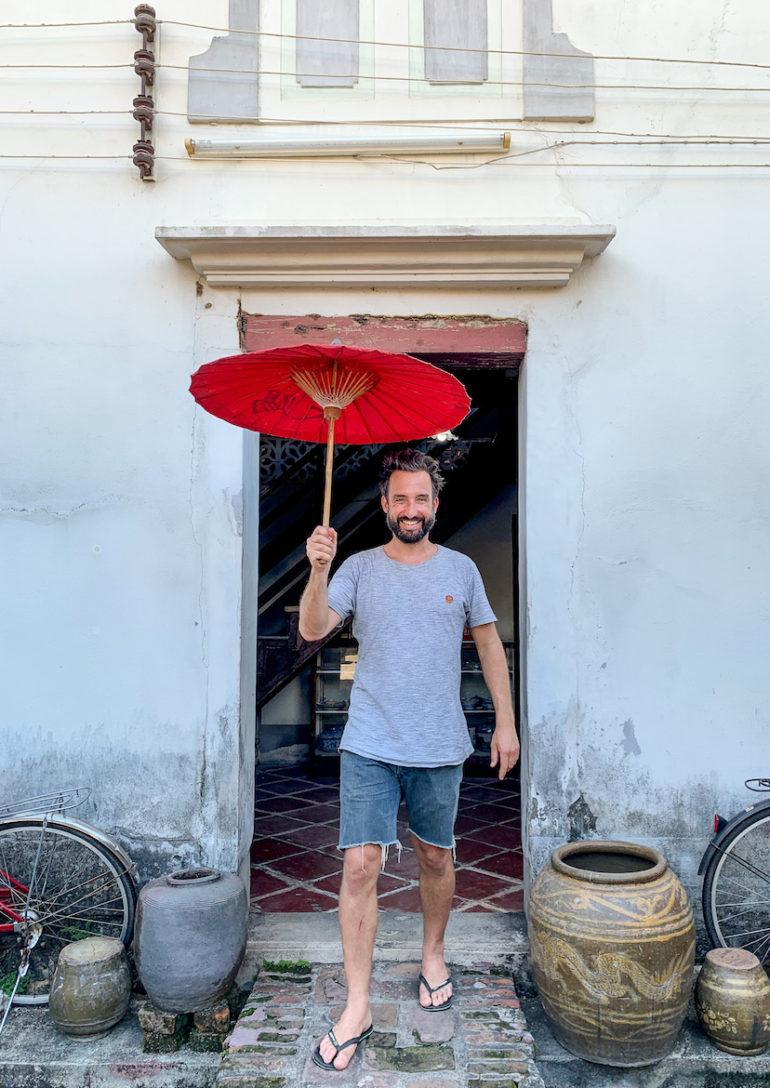 Marco Buch mit Sonnenschirm vor dem 100 year old house.