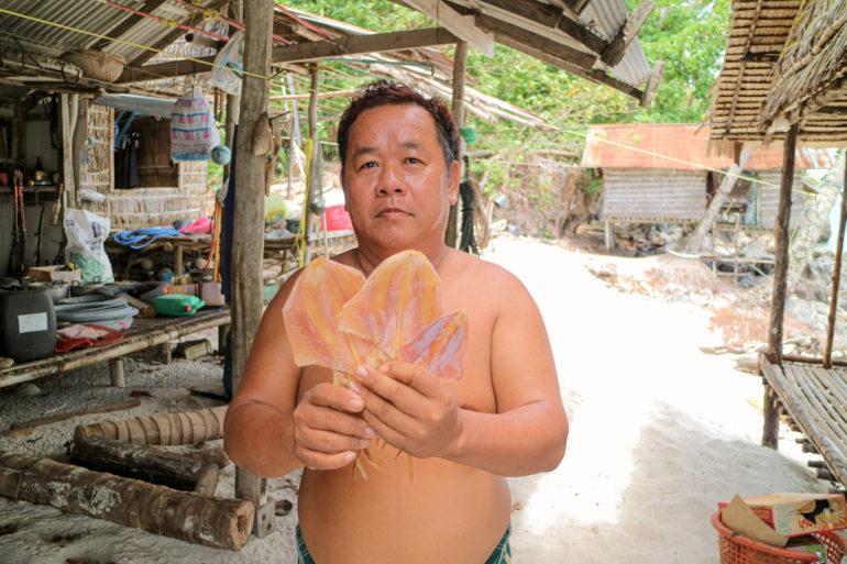 Mann mit getrocknetem Tintenfisch
