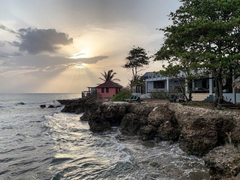 Jamaika Urlaub: Sonnenuntergang über Häusern und Felsen am Treasure Beach