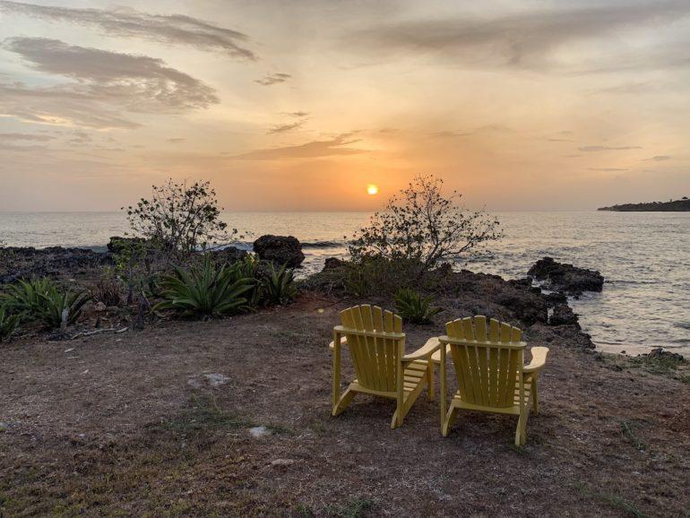 Jamaika Urlaub: Liegestühle vor Pflanzen und Meerl