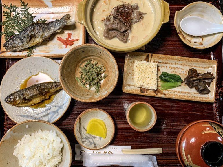 Teller und Schüsseln mit unterschiedlichen Speisen bei einer Japan Reise