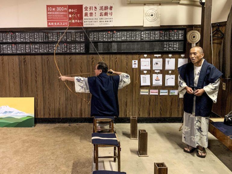 Zwei Bogenschützen vor einer beschrifteten Wand