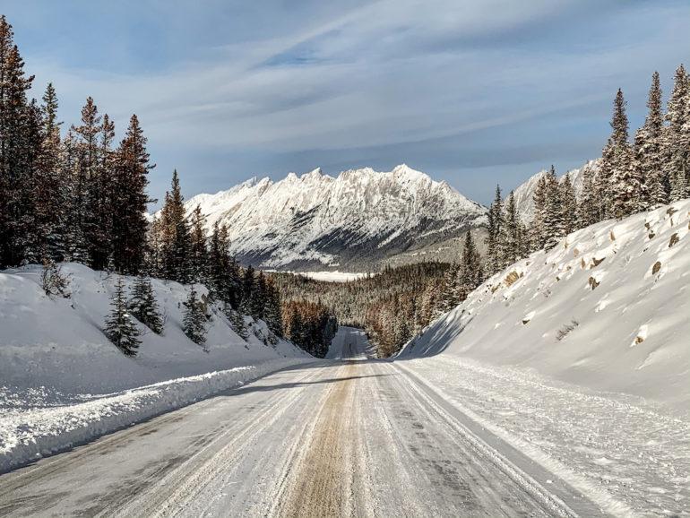 Alberta Highlights: Verschneite Strasse vor Bergen.
