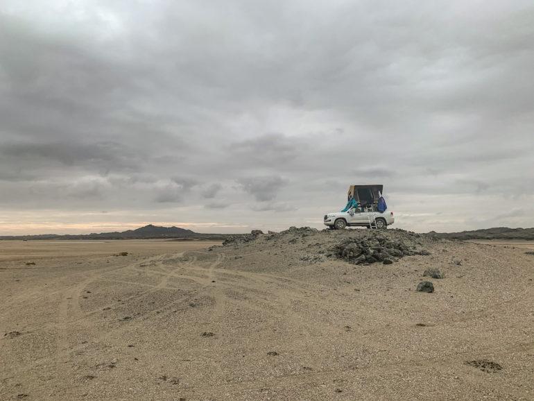 Geländewagen auf einem Felsen am Strand im Oman