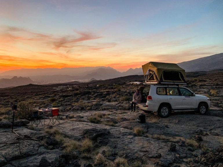 Geländewagen auf felsen vor Sonnenuntergang im Oman