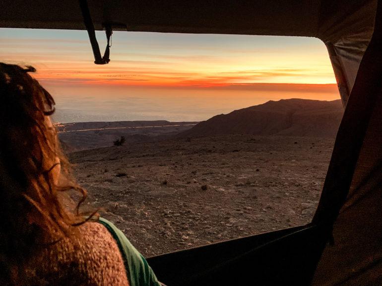 Frau blickt aus Dachzelt auf Oman Roadtrip