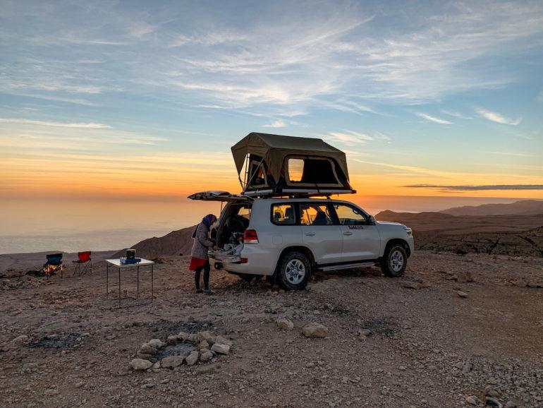 Frau neben Geländewagen auf einem Oman Roadtrip