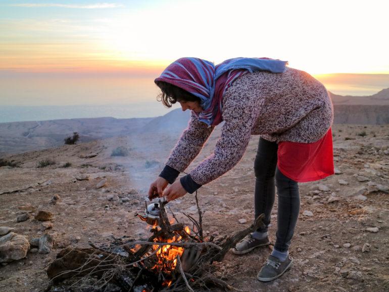 Frau bereitet Tee über Feuer zu
