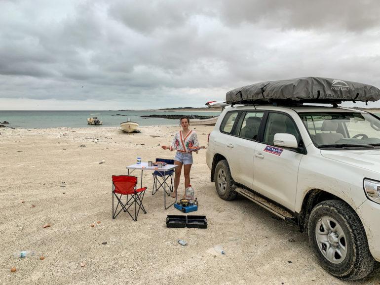 Frau mit Geländewagen am Strand im Oman