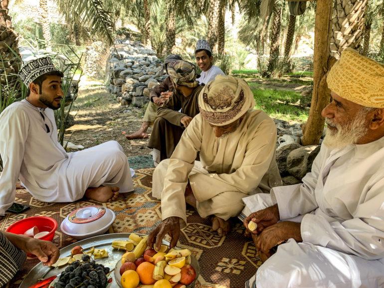 Omanische Männer trinken Kaffee in einer Oase