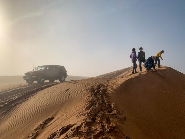 Geländewagen und Menschen in den Dünen von Sharquiya Sands